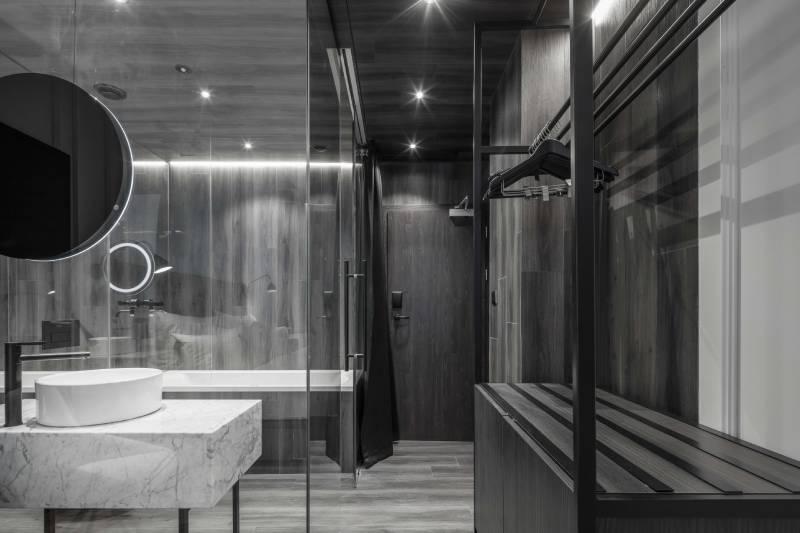 Koupelna v hotelovém pokoji hotelu Pytloun v Praze, na stěnách a podlaze jsou použité vinylové dílce