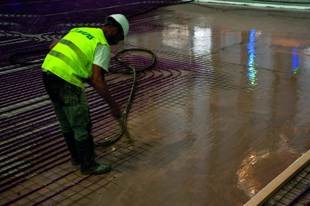 Pracovník s vestou s nápisem Mapei a s ochrannou přilbou připravuje podklad podlahy v katedrále