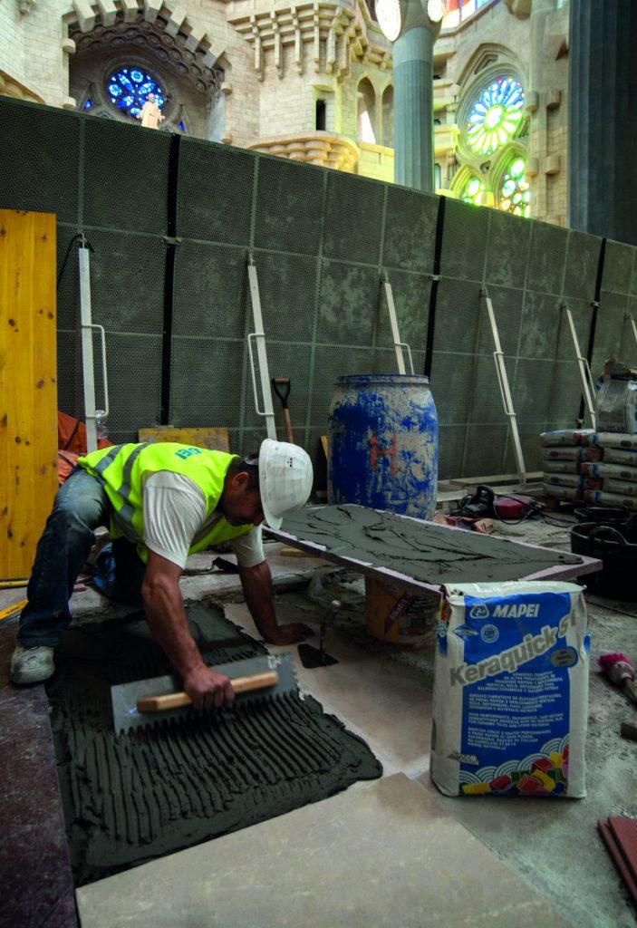 Pracovník ve vestě s nápisem Mapei a s ochrannou přilbou nanáší na podlahu lepidlo na přilepení dlažby, před ním je pytel s nápisem Keraquick S1, vedle něj připravená velkoformátová dlaždice