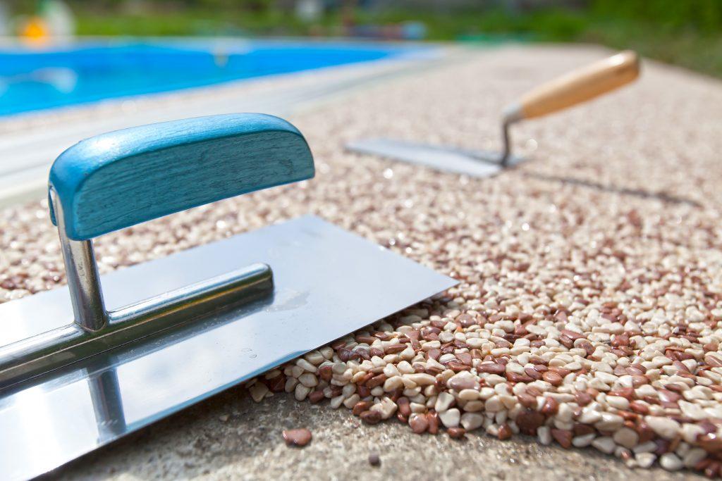 hladítka urovnávají kamínky na betonovém chodníku okolo bazénu
